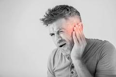 Mannen som har örat, smärtar att trycka på hans smärtsamma huvud som isoleras på grå färger arkivbilder