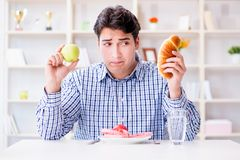 Mannen som har dilemma mellan sund mat och bröd, i att banta, lurar Arkivbilder