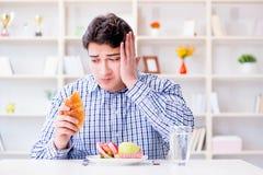 Mannen som har dilemma mellan sund mat och bröd, i att banta, lurar Royaltyfri Fotografi