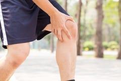 Mannen som har knäet, smärtar, medan öva, sportskadabegreppet Arkivfoton