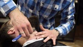 Mannen som har rakning på barberaren, shoppar tätt upp Den yrkesmässiga barberaren som använder den raka rakkniven med det skarpa arkivfilmer