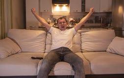 Mannen som hemma håller ögonen på en lek att sitta på soffan i aftonen på TV, stöttar fotbollslaget, jublar målet arkivfoton