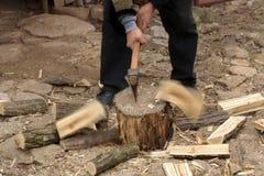 Mannen som hugger av brandträ, loggar med rörelsesuddighet royaltyfria bilder