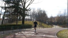 Mannen som in joggar, parkerar på kursspåret med closeupsikt av hans ben arkivfilmer