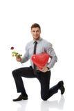 Mannen som knäfaller med den röda rosen, och hjärta sväller Arkivfoto