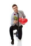Mannen som knäfaller med den röda rosen, och hjärta sväller Royaltyfria Foton