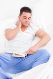 Mannen som ligger i sänglidande från hals, smärtar läseboken arkivbild