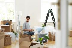 Mannen som packar upp material från lådan, boxas efter förflyttning till det nya hemmet fotografering för bildbyråer