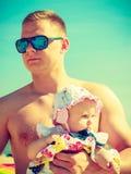 Mannen som poserar med, behandla som ett barn på sommar Royaltyfri Fotografi