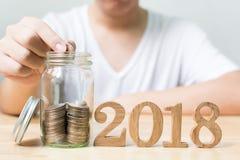 Mannen som sätter myntet i krus med det wood numret 2018 år, sparar pengar a Royaltyfri Foto