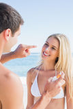 Mannen som sätter solkräm på gulliga flickvänner, nose Royaltyfria Bilder