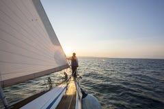 Mannen som ser det härliga havet från pilbåge av, seglar fartyget fotografering för bildbyråer