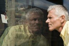Mannen som ser skänken shoppar in, fönstret Royaltyfria Foton