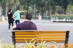 Mannen som sitter på bänk, parkerar royaltyfria foton