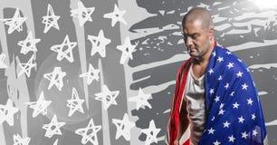 Mannen som slås in i amerikanska flaggan som ser ner mot grå färger, räcker den utdragna amerikanska flaggan och signalljuset Royaltyfria Foton
