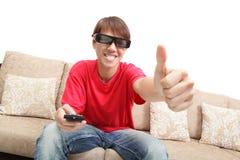 Mannen som slitage exponeringsglas 3d, håller ögonen på upp tv:n och tumen Fotografering för Bildbyråer