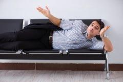 Mannen som sover på stolarna i flygplats royaltyfri bild