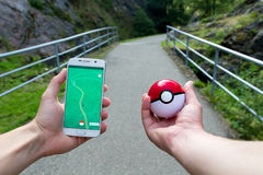 Mannen som spelar Pokemon, går utomhus- Royaltyfria Foton