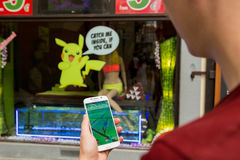 Mannen som spelar Pokemon, går utomhus- Arkivbilder