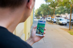 Mannen som spelar Pokemon, går utomhus- Royaltyfria Bilder