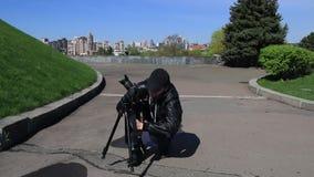 mannen som squatting med en tripod, gör fotolandskapet för timelapse lager videofilmer
