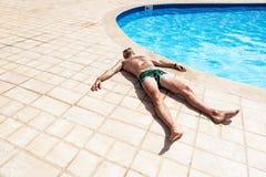 Mannen som sunning vid pölen Royaltyfria Bilder