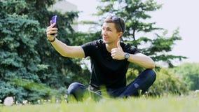 Mannen som talar i video pratstund via mobiltelefonen som sitter på gräset parkerar och talar in, med vänner vid den videopd appe arkivfilmer