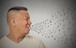 Mannen som talar med alfabet, märker att komma ut ur öppen mun Arkivfoton