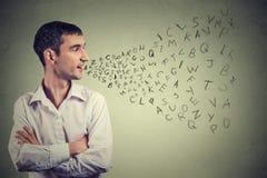 Mannen som talar med alfabet, märker att komma ut ur hans mun Kommunikation information, intelligensbegrepp arkivfoto