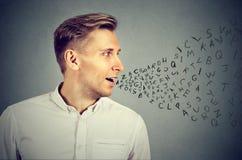 Mannen som talar med alfabet, märker att komma ut ur mun royaltyfri foto
