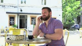 Mannen som talar vid smarphone, ler för kamera lager videofilmer