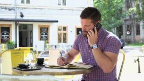 Mannen som talar vid smartphonen, gör anmärkningar till anteckningsboken, glidareskottet som är högert lager videofilmer