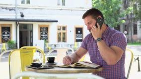 Mannen som talar vid smartphonen, gör anmärkningar till anteckningsboken, glidareskottet som lämnas lager videofilmer