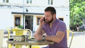 Mannen som talar vid telefonen under att äta frukosten, glidare sköt rätt arkivfilmer
