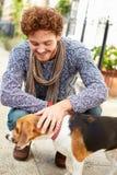 Mannen som tar hunden för, går på stadsgatan Arkivbilder