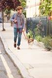 Mannen som tar hunden för, går på stadsgatan Arkivfoton