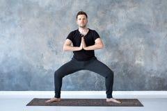 Mannen som utarbetar, yoga, pilates, konditionutbildning, gudinna poserar eller rudrasanaen royaltyfri fotografi