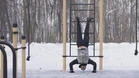 Mannen som utbildning skjuter, ups övning med ben som lyfter upp på vintersportjordning arkivbilder