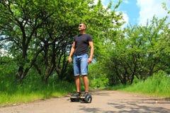 Mannen som utomhus rider en elektrisk sparkcykel - sväva brädet, det smarta jämviktshjulet, gyroskopsparkcykeln, hyroscooter, per Royaltyfri Bild