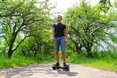 Mannen som utomhus rider en elektrisk sparkcykel - sväva brädet, det smarta jämviktshjulet, gyroskopsparkcykeln, hyroscooter, per Royaltyfria Bilder
