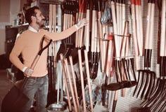 Mannen som väljer den nya skyffeln i trädgårds- utrustning, shoppar arkivfoton