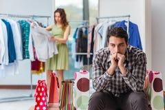 Mannen som väntar på hans fru under att shoppa för jul Arkivfoton