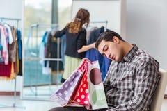 Mannen som väntar på hans fru under att shoppa för jul Royaltyfri Bild