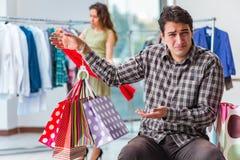 Mannen som väntar på hans fru under att shoppa för jul Arkivbilder