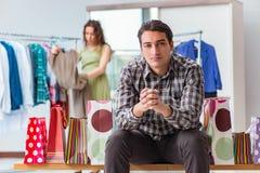 Mannen som väntar på hans fru under att shoppa för jul Royaltyfria Bilder