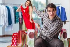 Mannen som väntar på hans fru under att shoppa för jul Arkivfoto