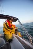 Mannen som vever en vinsch seglar på, fartyget i havet Royaltyfria Bilder