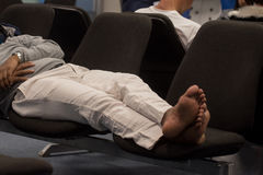 Mannen sover på flygplatsen royaltyfri bild