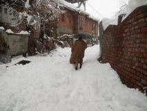 Mannen sparar sig från snö med paraplyet Royaltyfria Foton