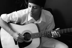 Mannen spelar den akustiska gitarren Arkivfoton